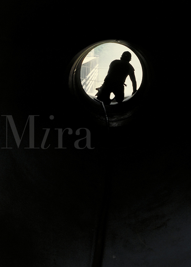 Silhouette of man working inside large pipe. Birmingham Alabama.
