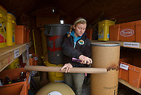 NWA Democrat-Gazette/BEN GOFF -- 03/09/15 Katie Anderson, staff biologist at Turpentine Creek Wildlife Refuge, sprays perfume on an empty cardboard tube while preparing a sensory enrichment for Bam Bam, a grizzly bear, to play with at the refuge near Eureka Springs on Monday Mar. 9, 2015. Anderson says the refuge tries to provide it's animals with a variety of sensory and nutritional enrichments, and says that even lions and tigers enjoy catnip and cardboard boxes. Anderson, an avid runner, has pledged to run the upcoming Victorian Classic 10K Run in Eureka Springs wearing a tiger costume if supporters donate at least $5,000 to help build larger habitat spaces at the refuge so the tigers can enjoy running themselves.