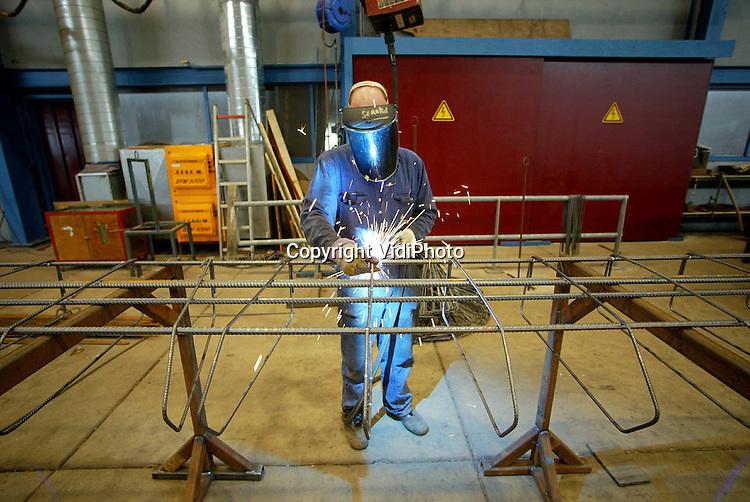Foto: VidiPhoto..DODEWAARD - Een werknemer van Romein Beton BV uit Dodewaard last de bewapening voor betonnen tunnelelementen die straks in de A59 bij Rosmalen geplaatst worden. De werkzaamheden vinden plaats in een van de twee gloednieuwe fabriekshallen van de betonfabriek. Romein is een van de weinige betonproducenten in Nederland die zelf ook de wapening maakt. Het bedrijf maakt op dit moment een flinke groei door en levert betonconstructies voor veel grote infrastructurele en bouwprojecten in ons land.