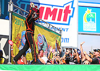 Sep 20, 2015; Concord, NC, USA; NHRA funny car driver Alexis DeJoria greets the fans during driver introductions prior to the Carolina Nationals at zMax Dragway. Mandatory Credit: Mark J. Rebilas-USA TODAY Sports