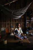 A family of farmers, U Hla Kyi (84) seen in his house in A Si Gyi village in Pyapon district of Myanmar. Hla Kyi lives with his 2 children who manage his 2 acre land where the family grows rice. His other son is a monk, whose portrait sits next to his bed.