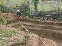 Grundschulklasse, Schulklasse legt einen Schulteich, Schul-Teich, Teich, Gartenteich, Garten-Teich im Schulgarten an, die ausgehobene Teichkuhle wird mit einem Maßband genau vermessen, die Wassertiefen-Zonierung ist gut zu erkennen