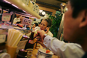 Woman speaking on the phone whilst in a carousel sushi restaurant, Shinjuku, Tokyo, Japan.