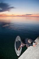 A stand up paddleboard paddler steps onto his board off the Lake Superior breakwater at Grand Marais Michigan.