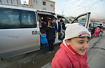 Displaced children climb out of a van at a school in Dohuk, Iraq. The children were displaced when the Islamic State group took over portions of the Nineveh Plains in 2014. Because they came from communities with Arabic curriculum schools, they often don't fit well in local schools that teach in Kurdish or Assyrian, so the Christian Aid Program Nohadra - Iraq (CAPNI) provides transportation to Dohuk, where they study in schools that meet their needs.