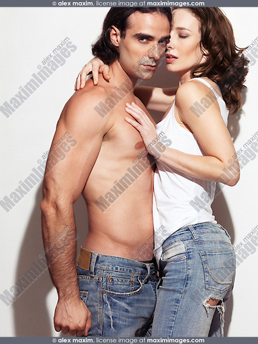 Expressive portrait of a sexy young man with bare torso wearing jeans embracing a young woman in tank top. Isolated on white background.