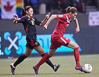 Christine Sinclair, right, of Canada dribbles past Dinora Garza of Mexico in the CONCACAF Olympic Qualifying semifinal match at BC Place in Vancouver, B.C., Canada Friday Jan. 27, 2012. Canada won the match 3-1 to earn a berth in 2012 London Olympics.
