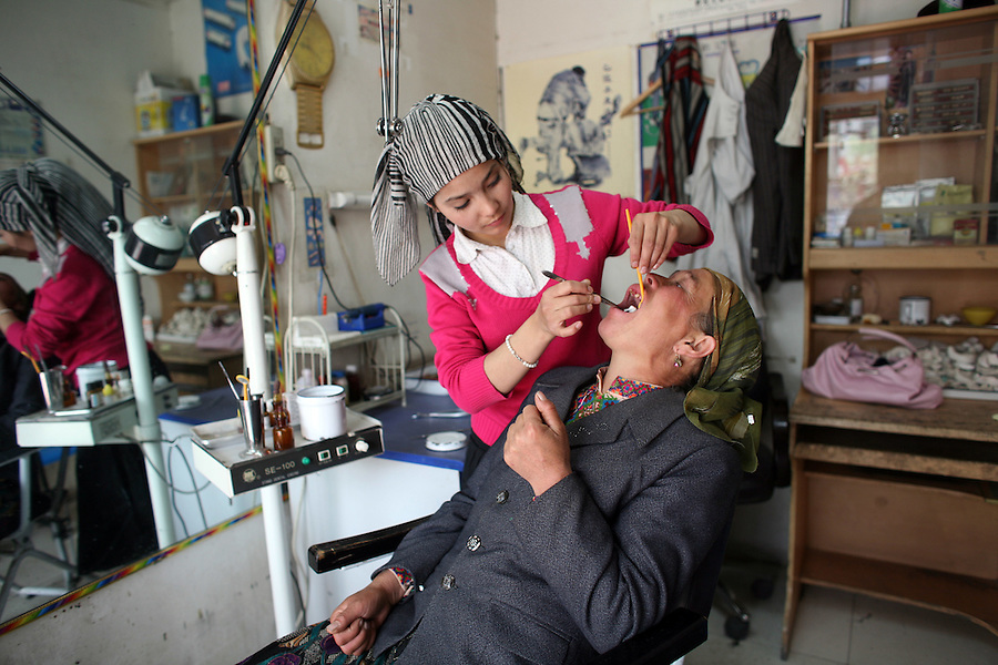 A young dentist removes a tooth from a patient in Khotan in Xingjinag Province. Half a billion people in China never brush their teeth, prompting the country's health chiefs to launch a major health education campaign.