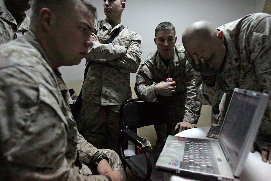 Lt. John McKinley (left) and the Marines of 2nd Platoon Golf Company 2nd Battalion 5th Marines, prepare for a raid on a suspected insurgent propagandist's home, plotting routes and positions, Tuesday, Jan. 11, 2005, in Ramadi, Iraq. The raid netted computers, DVDs, and other materials but the target was not apprehended.