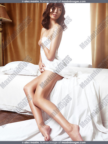 Beautiful young asian woman sitting naked on a bed covering with a bed sheet