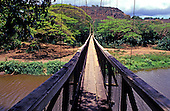 Long view of the old wooden-planked swinging Menehune Bridge over the Waimea River on the island of Kauai.