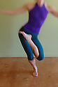 Dancing Woman's body (cropped at the neck) in yoga dance pose in a yoga studio. Soft focus Lensbaby image. High Grain.