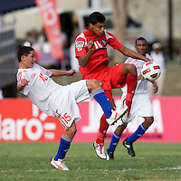 Osmani Capote (15) of Cuba fights for the ball with Jorman Aquilar (18) of Panama during the group stage of the CONCACAF Men's Under 17 Championship at Jarrett Park in Montego Bay, Jamaica. Panama tied Cuba, 0-0.
