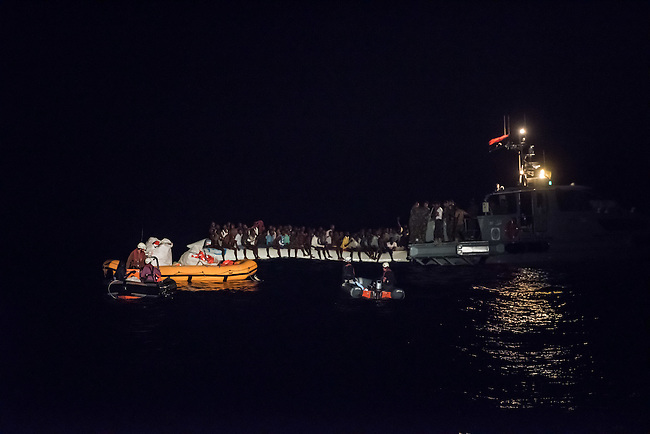 Die Sea Watch-2 Crew war am Freitag den 21. Oktober 2016 in den fruehen Morgenstunden waehrend ihrer 13. SAR-Mission vor der libyschen Kueste zu einer Position ausserhalb der 12 Meilenzone gerufen worden. Es war ein Fluechtlingsschlauchboot gesichtet worden. Als die Sea Watch-2 dort eintraf sah sie ca. 150 Menschen zusammengepfercht in einem ueberfuellten Schlauchboot sitzen. Eine Versorgung der Menschen auf dem Fluechtlingsschlauchboot mit Rettungswesten durch die Rettungs Boote der Sea Watch-2 wurde von der libyschen Kuestenwache unterbunden. Ein Soldat der Kuestenwache enterte das Schlauchboot vom Bug und machte sich dann an dem Aussenbordmotor zu schaffen. Auf dem Weg dahin schlug und trat er die Gefluechteten ein. Nach einigen Minuten entfernte sich das Boot der Kuestenwache. Dann verlor der Bug des Schlauchbootes seine Luft und es brach Panik bei den Gefluechteten aus. Sie sprangen in das Wasser und versuchten zum Schiff Sea Watch-2 zu gelangen. Die Crew warf ihnen Schwimmwesten und Rettungsringe zu, die Besatzungen der Rettungsboote der Sea Watch-2 zogen Menschen aus dem Meer, dennoch sind bis zu 30 Menschen ertrunken. Vier Ertrunkene konnten von der Sea Watch geborgen werden.<br /> Im Bild: Die Libysche Kuestenwache entert ein Fluechtlingsschlauchboot und um zu dessen Aussenbordmotor zu gelangen. Im Vordergrund: Die abgedraengten Rettungsboote der Sea Watch-2.<br /> 21.10.2016, Mediterranean Sea<br /> Copyright: Christian-Ditsch.de<br /> [Inhaltsveraendernde Manipulation des Fotos nur nach ausdruecklicher Genehmigung des Fotografen. Vereinbarungen ueber Abtretung von Persoenlichkeitsrechten/Model Release der abgebildeten Person/Personen liegen nicht vor. NO MODEL RELEASE! Nur fuer Redaktionelle Zwecke. Don't publish without copyright Christian-Ditsch.de, Veroeffentlichung nur mit Fotografennennung, sowie gegen Honorar, MwSt. und Beleg. Konto: I N G - D i B a, IBAN DE58500105175400192269, BIC INGDDEFFXXX, Kontakt: post@christian-ditsch.de<br /> Bei der Bearbe