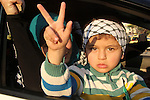 A Palestinian child marks victory sign during a rally in Gaza city on December 31, 2012. The Gaza branch of Palestinian president Mahmud Abbas's Fatah party said on Friday it will mark its anniversary in the Hamas-ruled enclave after an accord between the two factions. Photo by Ezz al-Zanoon