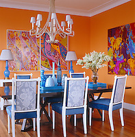 The dining room is decorated in dramatic orange with vivid turquoise accents in the upholstery of the chairs and a collection of glass and ceramic figurines