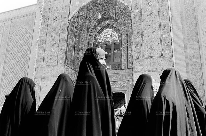 Iraq. Najaf. Iraqi women near the entrance to the mosque, Holy Shrine of Imam Ali. The women wear the abaya and the hidjab (islamic headscarf) on their heads to cover their hair. The abaya, sometimes also called aba, is a simple, loose over-garment, essentially a robe-like dress, worn by some women in parts of the Islamic world. Traditional abaya are black and may be either a large square of fabric draped from the shoulders or head or a long caftan. The abaya covers the whole body except the face, feet, and hands. The word hijab (or hidjab) refers to both the veil covering the head and traditionally worn by muslim women (Islamic headscarf), but also the  modest muslim styles of dress in general. Imam Ali was the cousin and son-in-law of the Islamic prophet Muhammad and was the first male convert to Islam. Shias regard Ali as the first Imam and consider him and his descendants the rightful successors to Muhammad. 26.02.04 © 2004 Didier Ruef .