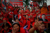 """Supporters hold pictures of ousted premier Thaksin Shinawatra as they celebrate branding as red the village of Suan Mon near Udon Thani in northeastern Thailand June 25, 2011. Regional leaders of Thailand's red-shirt protest movement held traditional Buddhist ceremony to launch 38 villages designated as """"Red Shirt Village of Democracy."""" The red shirts, supporters of ousted premier Thaksin Shinawatra, have been branding hundreds of villages as red to rally behind Thaksin's sister, Yingluck, who is leading the opposition ahead of July 3 general elections.   REUTERS/Damir Sagolj (THAILAND)"""
