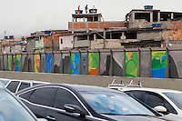"""Complexo da Mare, a massive network of favelas that sits alongside the Linha Vermelha ( Red Line ), the main highway from the Rio de Janeiro international airport to the city centre - since 2010 the community has been fenced off from the highway by huge Perspex panels - authorities claim they provide an acoustic barrier, locals describe it as a """"wall of shame"""",  another way of hiding poor people. Just before the Olympic Games the city began plastering the 3-metre-high, 7km stretch of panels with colorful Olympic posters showing the city´s main landscapes."""