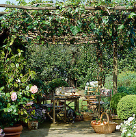 A table laid for lunch in the shade of an arbour with baskets filled with home-grown vegetables