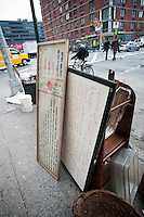 Signs and other dtritus outside the Manganaro Grosseria Italiana on Ninth Avenue in the Hell's Kitchen neighborhood of New York, seen on Monday, February 27, 2012.  The restaurant is to close today.  (© Richard B. Levine)