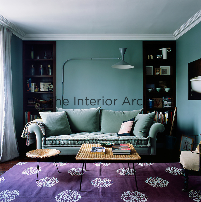 The blue of the walls and the mauve rug give the living room a cool ambiance. The room is simply furnished in a mix of styles