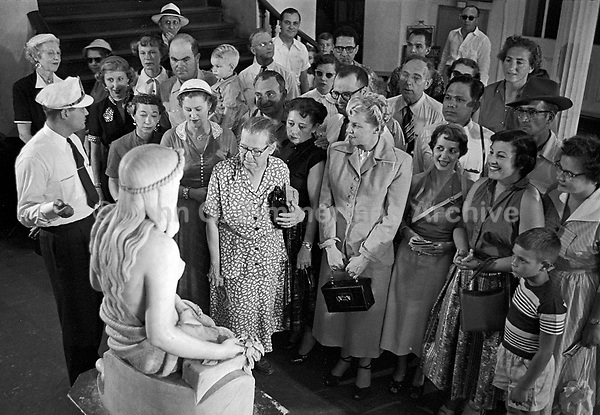 Museum guide discusses sculpture with visitors, Presbytere, New Orleans Louisiana, 1953. Credit: © John G. Zimmerman Archive