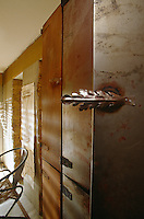 Built-in metal cupboards with a distressed rusting surface add to the industrial feel of this apartment