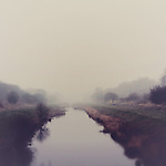 english fog surrounds a river on a winter's morning