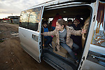 Displaced children on their way to school aboard a van in Seje, Iraq. The village was flooded with displaced families when the Islamic State group took over nearby portions of the Nineveh Plains in 2014. Because the displaced children came from communities with Arabic curriculum schools, they don't fit well in local schools that teach in Kurdish or Assyrian, so the Christian Aid Program Nohadra - Iraq (CAPNI) provides transportation to Duhok, where they study in schools that meet their needs.