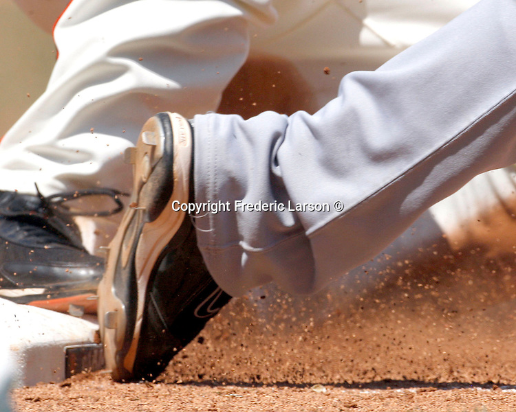 A detailed shot of a baseball players spikes leaving a base.