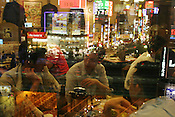 The view from inside an 'izakaya' restaurant, looking out to the neon lights of  Shinjuku, Tokyo, Japan.