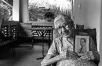 Christobelle Oorloff who tried to teach me English Literature, holding a photograph of her husband Cedric.<br />