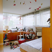 A child's bedroom is filled with light from wall-to-wall picture windows and the practical and functional built-in cupboards are constructed from plywood