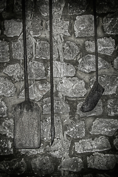 Old tools hanging against a stone wall