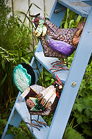 Whimsical chicken sculpture (art) on old ladder in Amy Stewart's garden