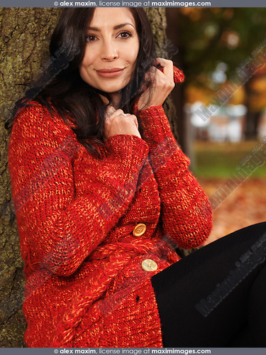 Beautiful smiling young woman cuddling up in a red sweater outdoors in fall