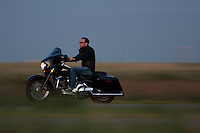 A man rides his black Harley down the highway