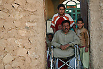 A man and his three sons watch from the doorway of their house as Iraqi troops backed by U.S. advisors search for weapons and insurgents in Al Cheb Allib, Iraq. The search turned up neither, and the villagers generally welcomed the troops' presence. Nov. 29, 2007. DREW BROWN/STARS AND STRIPES