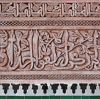 Kufic calligraphy in stucco from courtyard of Ben Youssef Madrasa, Medina, Marrakech, Morocco. This inscription is carved in Iraqi kufic style interwoven with a vegetal design and loops. The Madrasa is an Islamic theological college founded in the 14th century and rebuilt by the Saadians in the 1560s. It is named after the Almoravid Sultan Ali ibn Yusuf, who reigned 1106-42. Picture by Manuel Cohen