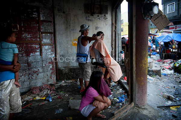 Magali Corouge / Documentography<br />Nov-Dec 2013, Tacloban, Leyte, Philippines.<br /><br />3 weeks after the disaster life starts to go back. In the streets of Tacloban, a man settles a improvised hairdressing salon  in the middle of fragments of a former shop.
