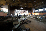 Mourners look around the interior of the municipal sports center in Rikuzentakata, Iwate Prefecture, Japan on 11 Mar 2012. .Photographer: Robert Gilhooly