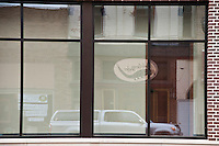The sign for the Driftless Angler fly shop is reflected in a building across the street in VIroqua Wisconsin.