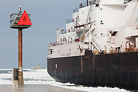 Cargo ship M/V Sam Laud passes a channel marker entering partially frozen Cleveland Harbor from the Cuyahoga River.