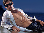 Muscular sexy young man in unbuttoned wet and dirty shirt lying on sand in the water