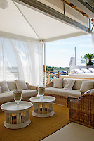 Long white curtains protect the outdoor seating area from the Adriatic sun