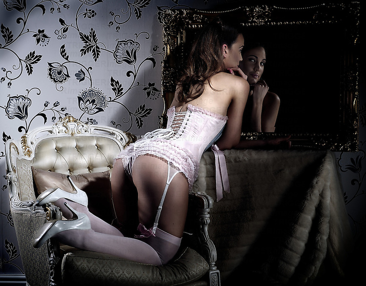 Young female in lingerie looking into a mirror.