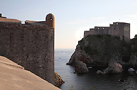 Western ramparts of the medieval walled city overlooking the Adriatic Sea (left) and the 11th century Lovrijenac Fortress (right), protecting the West of the city, Dubrovnik, Croatia. The city developed as an important port in the 15th and 16th centuries and has had a multicultural history, allied to the Romans, Ostrogoths, Byzantines, Ancona, Hungary and the Ottomans. In 1979 the city was listed as a UNESCO World Heritage Site. Picture by Manuel Cohen