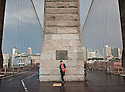 A girl takes a shelter under the Brooklyn bridge arches waiting for the rain to stop.