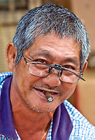 A Chinese man smokes is cheap cigars.